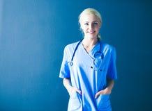 Портрет усмехаясь доктора в форме стоя на серой предпосылке Стоковые Изображения