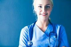 Портрет усмехаясь доктора в форме стоя на серой предпосылке Стоковое Фото
