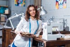 Портрет усмехаясь европейского модельера стоя рядом с швейной машиной держа подарок упаковал в бумаге ремесла внутри стоковая фотография rf
