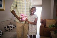 Портрет усмехаясь девушки давая подарок к отцу Стоковая Фотография