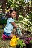 Портрет усмехаясь девушки вставать пока выкапывающ почву с лопаткой Стоковые Фото