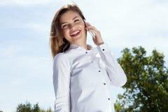Портрет усмехаясь девушки говоря мобильным телефоном Стоковое Фото