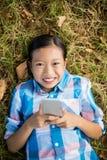 Портрет усмехаясь девушки лежа на траве и используя мобильный телефон Стоковое фото RF