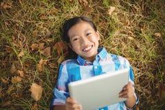 Портрет усмехаясь девушки лежа на траве и используя цифровую таблетку Стоковое фото RF