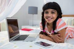 Портрет усмехаясь девушки лежа с мобильным телефоном и компьтер-книжкой на кровати Стоковое Фото