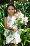 Портрет усмехаясь девушки держа букет цветков стоя между заводами Стоковые Фото