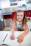 Портрет усмехаясь девушки делая домашнюю работу в кухне Стоковая Фотография RF