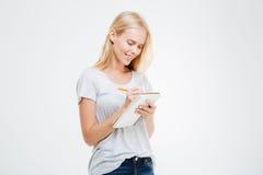 Портрет усмехаясь девушки делая примечания в блокноте Стоковые Фотографии RF