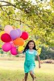 Портрет усмехаясь девушки играя с воздушными шарами в парке Стоковые Фотографии RF