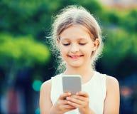 Портрет усмехаясь девушки играя с мобильным телефоном Стоковые Изображения