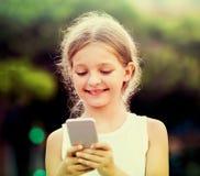 Портрет усмехаясь девушки играя с мобильным телефоном Стоковая Фотография RF