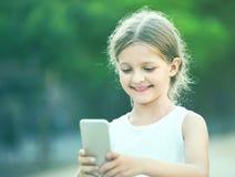 Портрет усмехаясь девушки играя с мобильным телефоном Стоковое Изображение