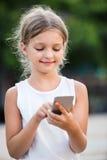 Портрет усмехаясь девушки играя с мобильным телефоном Стоковое фото RF