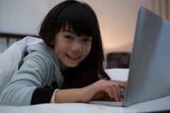 Портрет усмехаясь девушки используя компьтер-книжку на кровати Стоковая Фотография RF
