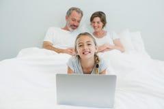Портрет усмехаясь девушки используя компьтер-книжку пока родители отдыхая в предпосылке Стоковые Изображения RF