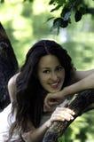 Портрет усмехаясь девушки сидя на дереве Стоковые Изображения