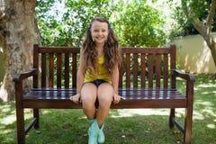 Портрет усмехаясь девушки сидя на деревянной скамье Стоковые Фото