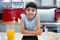 Портрет усмехаясь девушки сидя с таблеткой и завтраком в кухне Стоковые Фото