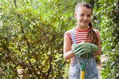 Портрет усмехаясь девушки стоя с садовничая вилкой против заводов Стоковые Изображения