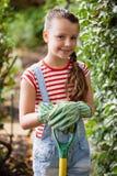 Портрет усмехаясь девушки стоя с садовничая вилкой Стоковые Изображения