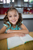 Портрет усмехаясь девушки с книгой в кухне Стоковое Фото