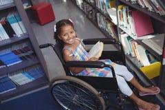 Портрет усмехаясь девушки с книгой на кресло-коляске Стоковые Фото