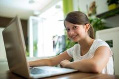 Портрет усмехаясь девушки с компьтер-книжкой в живущей комнате Стоковое Изображение