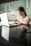 Портрет усмехаясь девушки с компьтер-книжкой в живущей комнате Стоковая Фотография