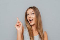Портрет усмехаясь девушки указывая палец вверх на copyspace Стоковые Фото