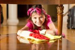 Портрет усмехаясь деревянного стола девушки полируя с тканью Стоковое фото RF
