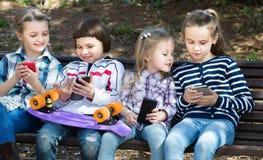 Портрет усмехаясь детей играя с телефонами Стоковые Фотографии RF