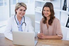 Портрет усмехаясь женских доктора и пациента сидя на столе Стоковое фото RF