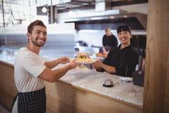 Портрет усмехаясь женских шеф-повара и кельнера держа плиту на счетчике Стоковое Изображение