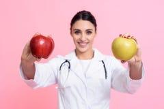 Портрет усмехаясь женского доктора при стетоскоп держа красные и желтые изолированные яблока Стоковое Фото