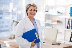 Портрет усмехаясь женского доктора держа доску сзажимом для бумаги Стоковые Фото