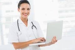 Портрет усмехаясь женского доктора используя компьтер-книжку Стоковая Фотография RF