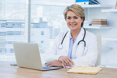 Портрет усмехаясь женского доктора сидя на столе с компьтер-книжкой Стоковые Изображения RF