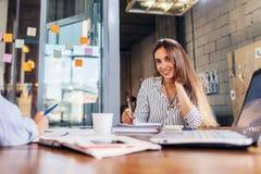 Портрет усмехаясь женского сочинительства работника офиса смотря камеру сидя на конференц-зале во время встречи Стоковая Фотография