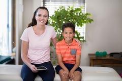 Портрет усмехаясь женского терапевта держа цифровое усаживание с рукой вокруг мальчика на кровати Стоковое Изображение RF