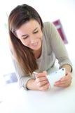 Портрет усмехаясь женщины брюнет используя smartphone Стоковые Фото