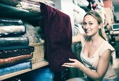 Портрет усмехаясь женщины выбирая одеяло Стоковые Изображения