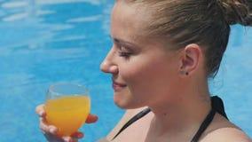 Портрет усмехаясь женщины выпивая стекло апельсинового сока в бассейне сток-видео