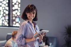 Портрет усмехаясь женщины в офисе с таблеткой стоковая фотография rf