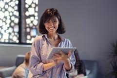 Портрет усмехаясь женщины в офисе с таблеткой стоковое изображение rf