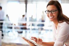 Портрет усмехаясь женщины в офисе с таблеткой Стоковые Изображения