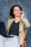Портрет усмехаясь женщины говоря на мобильном телефоне при компьтер-книжка лежа на ее коленях стоковые фото
