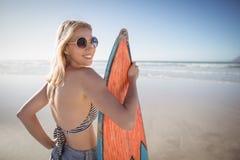 Портрет усмехаясь женщины держа surfboard на пляже Стоковая Фотография RF