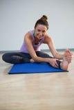 Портрет усмехаясь женщины делая протягивающ тренировку Стоковое Изображение RF