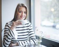 Портрет усмехаясь женщины имея кофе на таблице кафа Стоковое Изображение