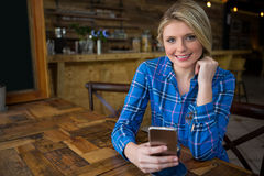 Портрет усмехаясь женщины используя мобильный телефон в кофейне Стоковое фото RF